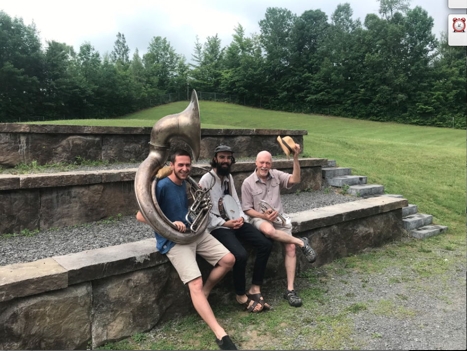 3 musiciens avec leurs instruments à l'extérieur dans un paysage verdoyant.